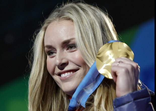 Lindsey Vonn shows the gold medal she won in the women's downhill ski race during the medal ceremony at the Vancouver 2010 Olympics in Whistler, British Columbia.