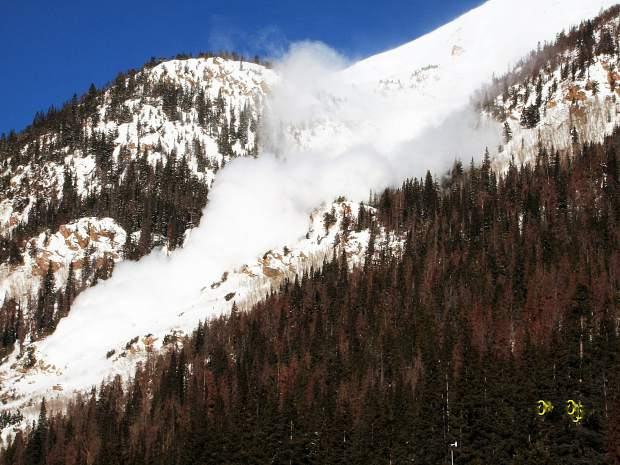 An avalanche cascades down toward an avalanche-deflection berm near Mount Bethel just east of the Continental Divide in March 2010.