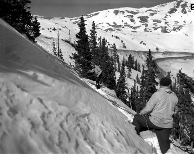 Ted Bakken receives a charge from Harold McMillian on the west side of Loveland Pass in the Little Professor slide area in 1954.