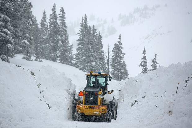 A tractor removes snow along Interstate 70 during snowstorm Thursday, March 7, at Loveland Pass.