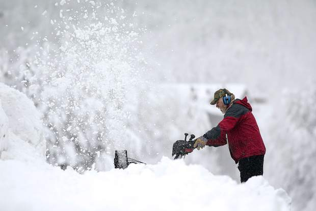 Dale Butler clears snow off his driveway along 5th Avenue with the snow removal machine Thursday, March 7, in Frisco.