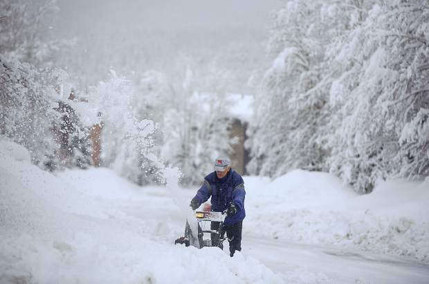 Mike Keaveney clears snow off his driveway along 5th Avenue with the snow removal machine Thursday, March 7, in Frisco.