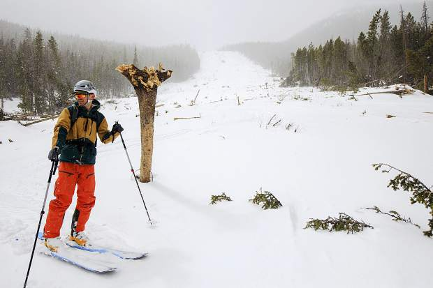 Boulder resident Taylor Kravits pauses to view the avalanche slide path March 23, below Peak One near Frisco.