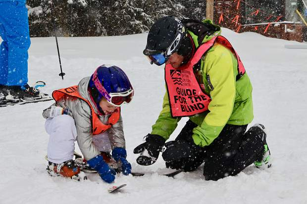 Breckenridge Outdoor Education Center guide Liam Matthews helps a youngster named Zoey, 5, make a snowball during this past weekend's United States Association of Blind Athletes Winter Festival event at Breckenridge Ski Resort, held in conjunction with the Breckenridge Outdoor Education Center.