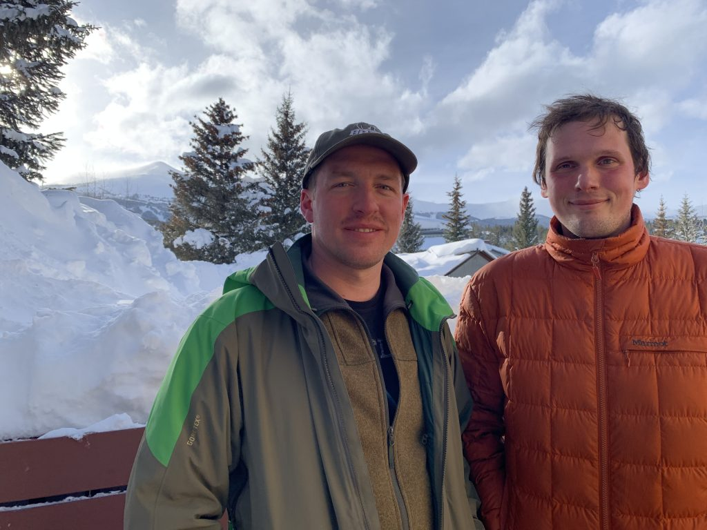 Ryan Zabik (left) and his friend George Micah Woods pose for a photograph in Breckenridge just over 24 hours after they both were caught in an in bounds avalanche at Breckenridge Ski Resort's Peak 8 (in view behind them). The duo was traversing from the top of the Imperial Express SuperChair to ski Whale's Tail when they were caught in the slide.