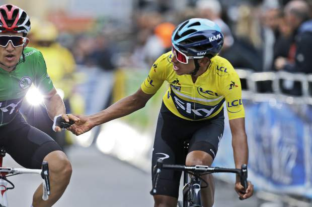 Colombia's Egan Arley Bernal Gomez, wearing the overall leader's yellow jersey, thanks teammate Poland's Michal Kwiatkowski, wearing the best sprinter's green jersey, as they cross the finish line of the eighth stage of the Paris Nice cycling race with start and finish in Nice, southeastern France, Sunday, March 17, 2019. (AP Photo/Claude Paris)
