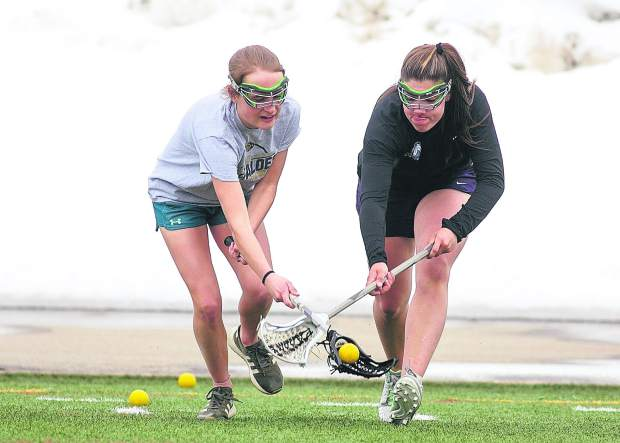 Members of the Summit High School girls lacrosse team compete for a loose ball on Wednesday, March 27, at Tiger Stadium near Frisco.