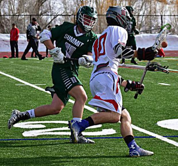 A Summit High School boys varsity lacrosse player defends possession by Steamboat Spring on Tuesday during the Tigers' 14-2 loss to the Sailors in Steamboat. The Tigers were within 6-2 at halftime after a strong first-half defensive performance.