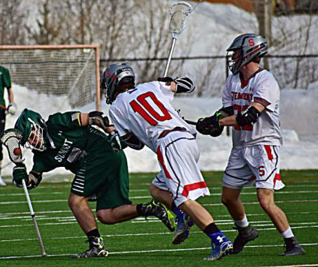 A Summit High School boys varsity lacrosse player attempts to retain his balance and possession of the ball during the Tigers' 14-2 loss to the Steamboat Springs Sailors on Tuesday in Steamboat. The Tigers were within 6-2 at halftime after a strong first-half defensive performance.