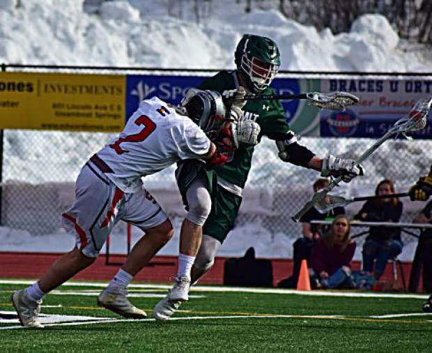 A Summit High School varsity boys lacrosse player fends off a defender during the Tigers' 14-2 loss to the Steamboat Springs Sailors on Tuesday in Steamboat. The Tigers were within 6-2 at halftime after a strong first-half defensive performance.