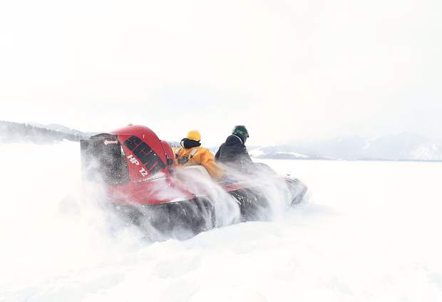 A hovercraft carrying Brian Metzger and Jesus Munoz speed across the snow and ice of Dillon Reservoir. The plan was to take Munoz out to the location. He would then dig a hole for the ice device, which Metzger would bring on a separate trip.