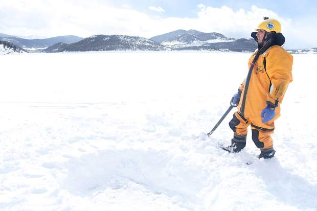 After digging a hole atop the thick ice of Dillon Reservoir, Jesus Munoz waits for Brian Metzger to return with the ice device.