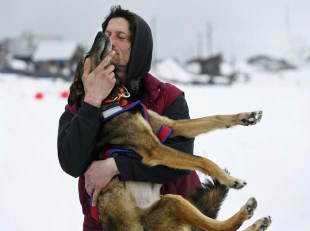 Iditarod musher Nicolas Petit hugs one of his dogs before they leave Unalakleet, Alaska, during the Iditarod Trail Sled Dog Race. Petit who was hours ahead in the Alaska race when his dogs refused to keep running is dismissing critics who say he ran them too hard and is chalking it up to a bad memory that spooked them.