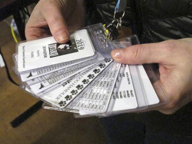 A collection of tags is shown that volunteer Jennifer Dowling keeps with her inside a hotel in Anchorage, Alaska, where she is helping to track the 1,000-mile Iditarod Trail Sled Dog Race this week.