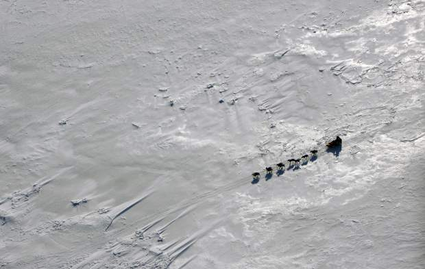 A team drives across Norton Bay just past the Shaktoolik, Alaska checkpoint on the Iditarod Trail Sled Dog Race trail in March 2009. Fifty-one mushers as of Friday are traveling long stretches between remote village checkpoints with no other company but the dogs pulling their sleds. However, their progress is monitored from several hotel rooms in Anchorage whose 24/7 occupants are the Iditarod's electronic eyes and ears.
