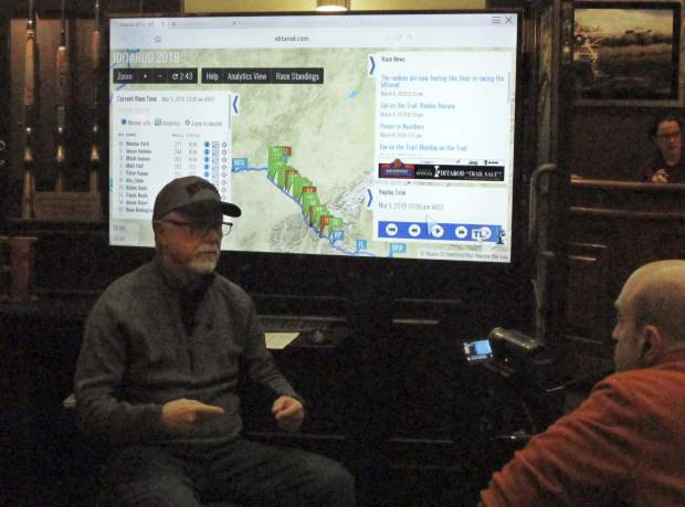 Iditarod spokesman Chas St. George, left, sits in front of a large screen set up inside a hotel in Anchorage, Alaska, for public updates in the 1,000-mile Iditarod Trail Sled Dog Race earlier this week. Technology has increasingly made the 47-year-old race more immediate to fans and safer for competitors, said St. George, acting CEO of the Iditarod Trail Committee, the race's governing board.