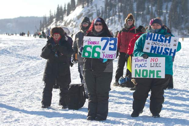 Melissa, center, and Sarah, right, Burnett, both of Fairbanks, hoist handmade signs for passing Iditarod mushers on the Chena River in Fairbanks, Alaska in MArch 2017. The women are avid race fans, following the mushers' GPS trackers obsessively and staying as up-to-date as possible with all race news. Technology has increasingly made the 47-year-old race more immediate to fans and safer for competitors, said Chas St. George, acting CEO of the Iditarod Trail Committee, the race's governing board.