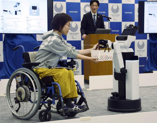 A robot passes a basket containing drinks to a woman in a wheelchair during an unveiling event in Tokyo on Friday. Organizers on Friday showed off robots that will be used at the new National Stadium to provide assistance for fans using wheelchairs.