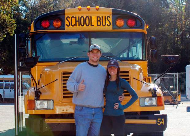 Jack Labosky, left, and Madi Hiatt pose after purchasing a school bus in Lynchburg, Virginia in October of last year. Labosky is a minor league pitcher in the Tampa Bay Rays organization, and he and Hiatt, his girlfriend, plan to live out of the bus during his first full professional season. The couple hopes to save money on rent to help offset Labosky's meager minor league salary.