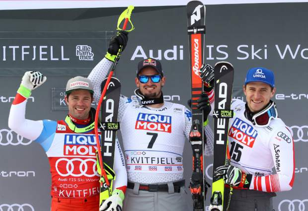 Italy's Dominik Paris, center, winner of an alpine ski, men's World Cup downhill, celebrates on the podium with second-placed Switzerland's Beat Feuz, left, and third-placed Austria's Matthias Mayer, in Kvitfjell, Norway, Saturday, March 2, 2019. (AP Photo/Alessandro Trovati)