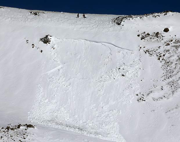 Loveland Ski Area's Ski Patrol, at top, intentionally trigger an avalanche during mitigation work for safety of the skiers before opening the slope Friday, March 15.