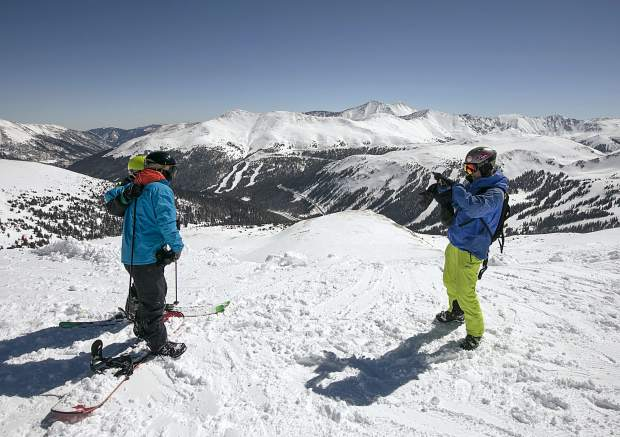 Ridge Cat riders take advantage of full view of the Continental Divide with a camera Friday, March 15, at Loveland Ski Area.