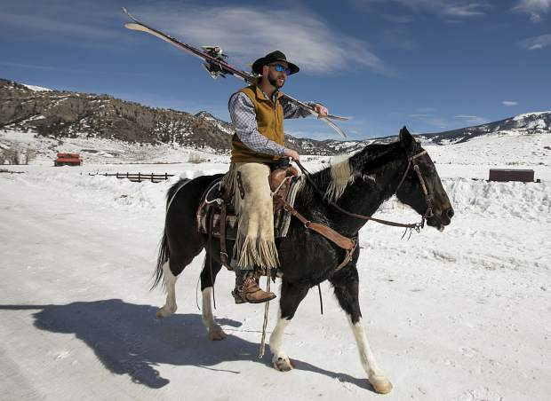 AJ Pestello lugs his skis over his shoulder while riding his trusty horse Jorge during skijoring practice on Wednesday, Feb. 27, at Pass Creek Ranch near Ute Pass, north of Silverthorne.