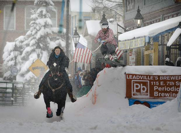 Savannah McCarthy and her horse, Tank, of New Mexico, pull a skier down Harrison Avenue during the 71st Leadville Ski Joring competition on Sunday afternoon, March 3, in Leadville.