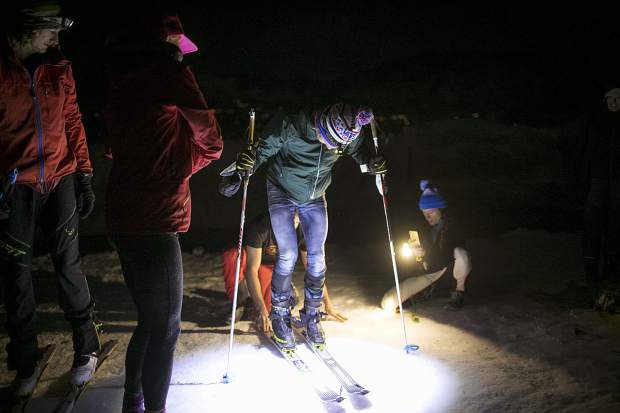 Carbondale's Sean Van Horn switches skis with the help of colleagues for another ascent lap on Buttermilk Mountain on Sunday night, March 17, near Aspen. Van Horn was attempting to break North America's record for the most vertical gain on skis in 24 hours.