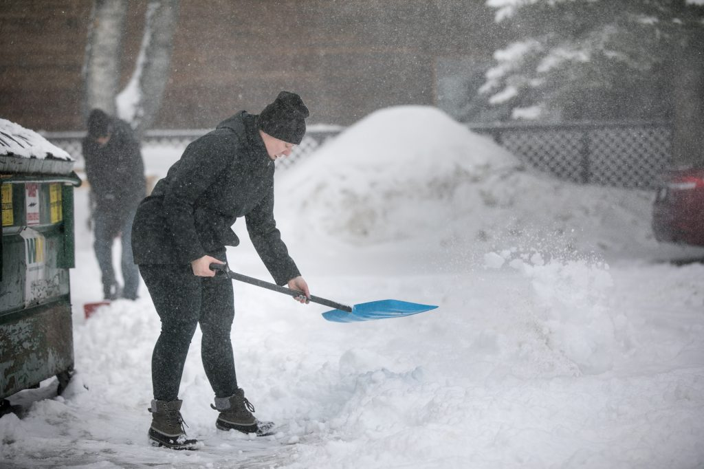 Kristin Keller, General Manager of Firsco Lodge, shovels snow off their parking lot Friday, March 1, along Main Street in Frisco.