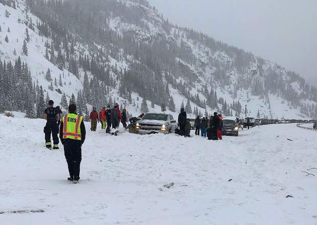 People work to clear the snow off Interstate 70 from an avalanche Sunday evening, March 3, near Frisco.