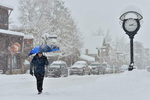 Mark Leon walks down Main Street Frisco holding an umbrella under a heavy snowfall on Sunday.