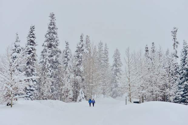People work their way through a winter wonderland Sunday in Frisco after heavy snowfall hit the county throughout the weekend.