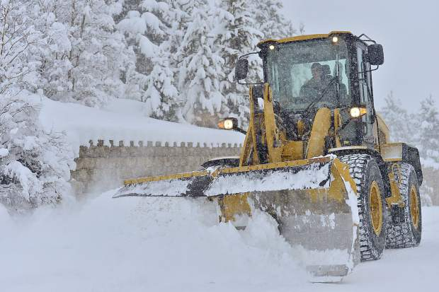 A front-end loader clears Frisco's streets of snow on Sunday.