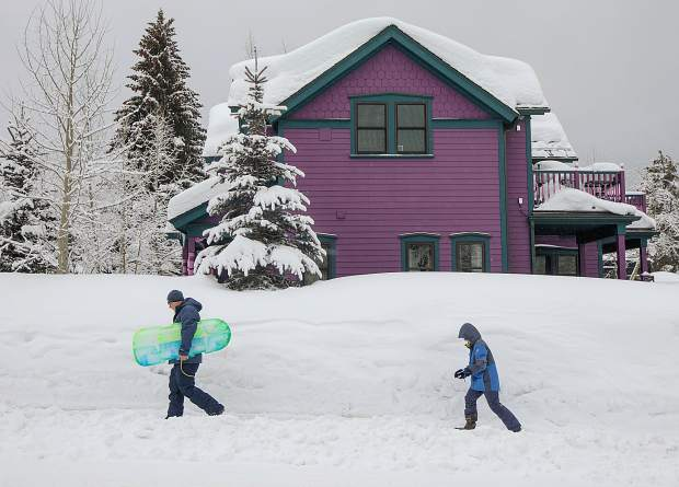 Breckenridge residents walk towards the Carter Park Sledding Hill Wednesday, March 13, in Breckenridge.