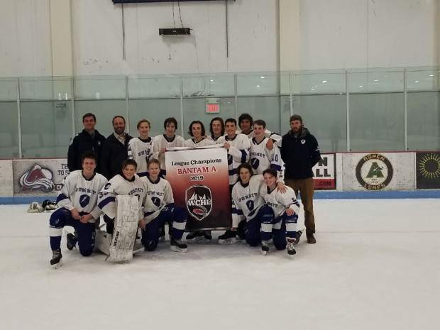 Coaches and players with Summit Youth Hockey's Bantam A team pose for a photograph with the banner that recognized them as the 2019 Western Colorado Hockey League champions.