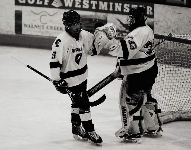 Summit Youth Hockey Bantam A forward Finn Theriault and goaltender Kaeden Edstrom embrace during a game earlier this season.