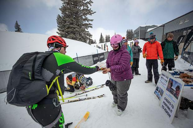 Rose Abello of Snowmass Tourism hands Grand Traverse racer Thomas Jaussi a piece of banana bread at the last checkpoint of the race from Crested Butte to Aspen on Saturday morning.  The Snowmass Tourism team put the station together to honor their coworker, Owen Green, and also his race partner Michael Goerne that passed away earlier this season training for this race. Green always enjoyed his banana bread with a view according to his coworkers.