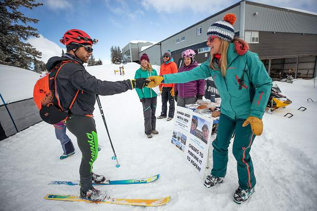 Julie Harding of Snowmass Tourism hands Grand Traverse racer Jeff Wanner a piece of banana bread at the last checkpoint of the race from Crested Butte to Aspen on Saturday morning.  The Snowmass Tourism team put the station together to honor their coworker, Owen Green, and also his race partner Michael Goerne that passed away earlier this season training for this race. Green always enjoyed his banana bread with a view according to his coworkers.