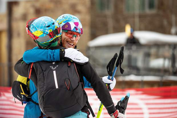 Teammates hug at the base of Aspen Mountain after completing the Power of Four ski mountaineering race on Saturday.