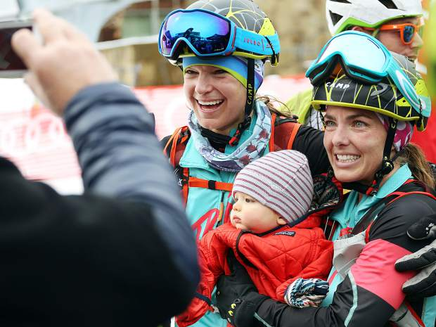 Jessie Young, right, holds her son, Ryder, while posing for a photo next to teammate Nikki LaRochelle after winning the 2019 Audi Power of Four ski mountaineering women's race on Saturday, March 2, 2019, in Aspen.