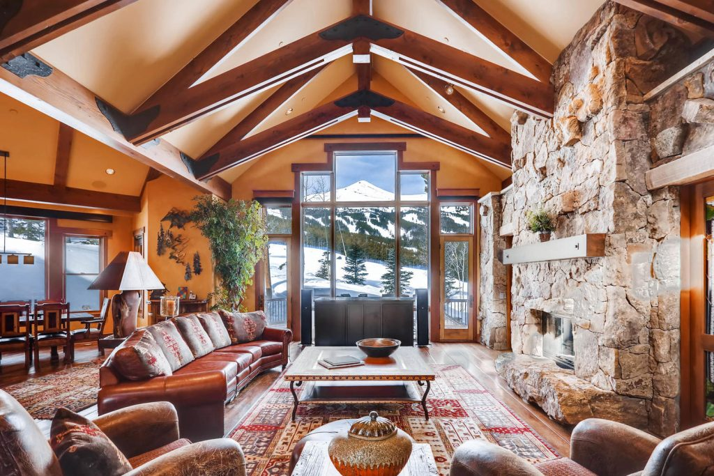 Located right on Trygve's run, this home is a classic mountain estate with elegant, rustic finishes like the striking exposed wood beams that complete the beautiful living area and its floor-to-ceiling views of the ski area.