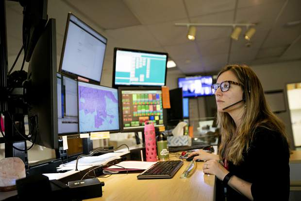 911 dispatcher Kandace Cornelsen coordinates with the 7 monitors while on duty Friday, April 26, at the Summit County Communications in Frisco.