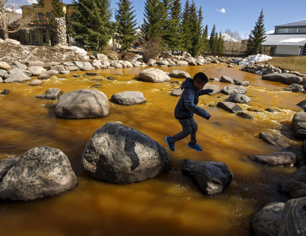 Nelson Lopez plays on the rocks as the Blue River in Breckenridge turned orange due spring runoff passing through old mines upstream Saturday afternoon, April 27. The river flows into the Dillon Reservoir, the source of water for Denver metro area.