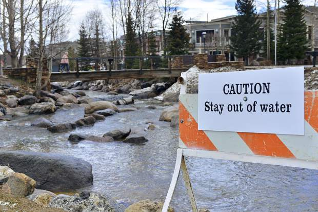 A sign warning people to keep out of the Blue River is posted in downtown Breckenridge by the Riverwalk Center on Sunday after the river was discolored a bright orange on Saturday.