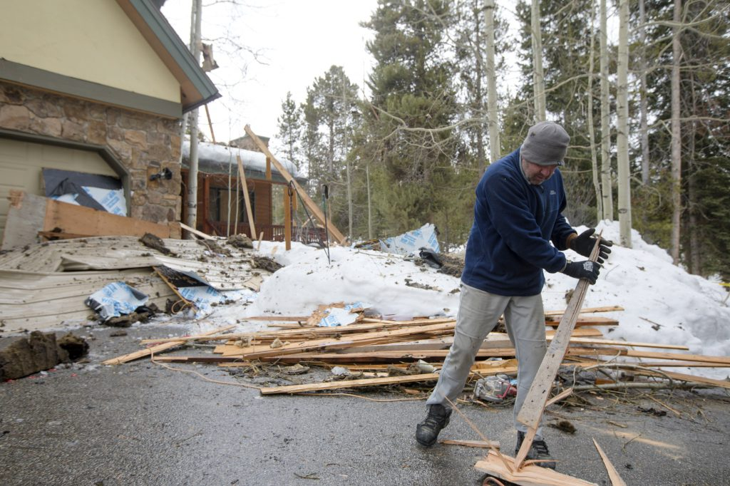 Tory Thompson cleans up the debris from the neighboring home Wednesday, April 3, along Royal Tiger Road in Breckenridge.