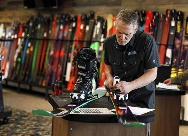 Christy Sports employee Dennis McLaughlin adjusts the bindings of rental skis for a client inside the renovated store location in Dillon Tuesday, April 2, along Highway 6.