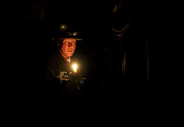 Country Boy Mine guide Paul Hintgen inhales before blowing out the candle light Wednesday, April 3, inside the mine near Breckenridge.