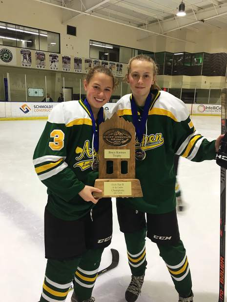 Taylor Ash, left, holds up a trophy won while playing with an Aspen-based double-A hockey team.