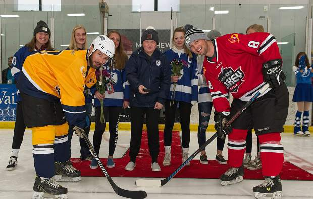 Summit High School junior Taylor Ash (center) ceremonially drops the puck alongside Summit Youth Hockey teammates as part of Saturday evening's championship game of the Summit Hockey Classic at Stephen C. West Ice Arena in Breckenridge.